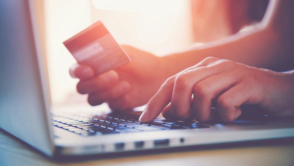 Hände, die Kreditkarte und Laptop benutzen. Online-Shopping
